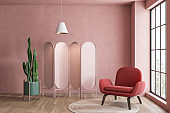 Pink living room with armchair and folding screen