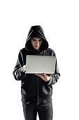 Serious young hacker with laptop, isolated