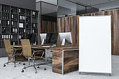 Gray office corner with vertical poster
