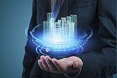 Businessman holding HUD city interface