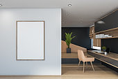 Beige and black home office interior with poster