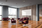 Wooden and gray office lounge area with poster