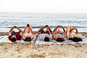 Young people lying on blanket on beach and surfing smartphones