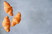 Three freshly baked croissants fly on grey background. Place for text. Creative bakery concept