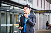 Businessman talking over mobile phone at airport