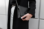 Fashionable women's black leather stylish bag. Modern young girl in stylish clothes. Fashion spring-autumn. New collection. Close-up.