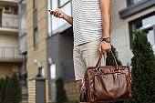 Successful young man in a stylish T-shirt in fashionable shorts with a vintage leather bag with a clock stands and looks at the mobile phone on the street. Close-up male body. Summer trendy menswear.