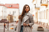 Model of a beautiful elegant woman in a chic beige trench coat with brown long hair in a stylish knitted sweater walks around the city on a bright spring day. Modern cute girl outdoors. Youth fashion.