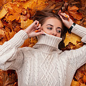 Modern stylish young woman with beautiful blue eyes with brown hair covers face with a vintage sweater on the background of autumn leaves. Cute girl is resting on orange foliage in a park.