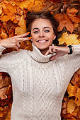 Top view of a wonderful young woman with a charming smile in a trendy knitted sweater on the background of orange-yellow foliage in the park. Positive girl lies in the forest on dry foliage. Autumn.