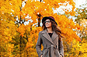Positive young woman with a beautiful smile with curly hair in an elegant hat in a stylish coat in trendy glasses enjoys the rest in the autumn park. Pretty happy hipster girl is relaxes outdoors.