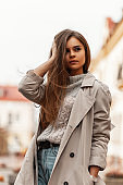 Pretty urban young woman straightens hair. Beautiful stylish girl a fashion model in a fashionable trench coat in a vintage gray knitted sweater walks around the city near the buildings. Spring style.