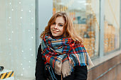 Charming young woman in a stylish winter coat in black gloves with a vintage woolen scarf is standing near a shop window decorated with a garland. Cheerful girl walks around the city