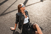 Pretty cheerful young hipster woman in a stylish leather jacket in trendy sunglasses in an elegant black skirt is resting on the asphalt on a sunny autumn day. Joyful girl with a smile enjoys vacation