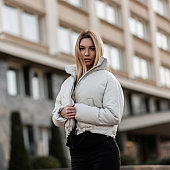 Beautiful fashionable young woman in a stylish white jacket stands in the city on the background of a modern building. Attractive girl fashion model in trendy autumn-spring clothes posing outdoors.