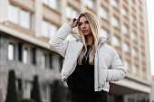 Glamorous young woman blonde in stylish clothes straightens hair. Beautiful trendy girl fashion model in a white fashionable seasonal jacket posing on a street in the city near a vintage building.