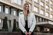 Young stylish model of a beautiful woman with long blond hair in a fashionable white jacket stands outdoors on an autumn day near a modern building. Urban girl in a trendy clothes walks in the city.