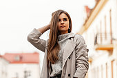 Trendy urban young woman in a fashionable knitted sweater in a stylish trench coat posing on a spring day in the street. Beautiful modern cute model girl enjoys a walk in the city. Spring fashion.