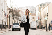 Slim urban young woman model with long blonde hair in a fashionable white jacket in stylish black jeans in a trendy leather bag walks along a city street on a warm autumn day. Modern girl is walking.