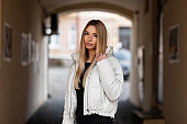 Beautiful young blonde woman with sexy lips in a black stylish sweater in a fashionable white winter jacket walks outdoors near a vintage building. Cute girl model stands on the street. Youth fashion.
