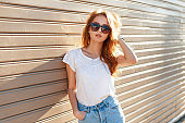 Stylish beautiful young model woman with sunglasses in a white T-shirt and blue vintage jeans near a wooden wall at sunset. Fashion hipster summer season