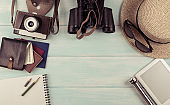 Travel set for tourist with documents, hat, photo camera, binoculars, notebook, and money on wooden background