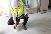 construction inspector sitting and checking cement floor in building