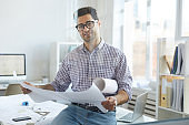 Smiling Engineer Holding Plans  at Workplace