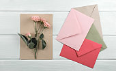 Wooden background with roses, envelope and eco paper