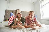 Young cheerful patriots with American flags lying on bed