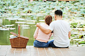 Couple sitting on pier outdoors
