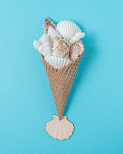Creative composition with seashells and ice cream cone on pastel blue background. Summer minimal concept.