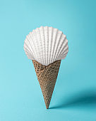 Creative composition with seashell and ice cream cone on pastel blue background. Summer minimal concept.