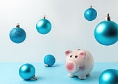 Piggy bank with Christmas decoration on blue table. Christmas or New Year minimal concept.