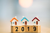 Wooden block word 2019 New year and house on top of coins stack.