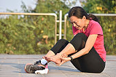 Female runner touching foot in pain due to sprained ankle