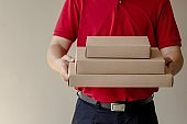 Delivery man standing with parcel post box on brown background.