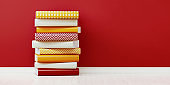 Colorful Books Sitting On Top Of Each Other In Front of Red Wall