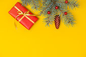 Christmas gift box with decoration on yellow background. Top view