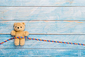 "World Autism Awareness day, mental health care concept with teddy bear and ribbon puzzle pattern. On blue background""n"