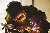 Worker in safety mask welds metal at industrial enterprises.