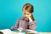 Beautiful girl sits at dchool desk, puts her hand in chin, attentively and enthusiastically reads the book aloud on blue isolated background. Child in first classroom for lessons.
