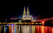 Night View of Cologne Cathedral (Kolner Dom) and Rhine river under the Hohenzollern Bridge,