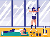 athletic women lifting dumbbells and doing chest push ups in gym