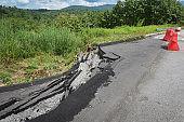 Asphalt road collapsed and cracks in the roadside - Road landslide subside with plastic barriers on uphill