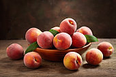 fresh peaches with leaves in a bowl