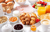 Breakfast with croissants, coffee, juice, meat, jam, cereals and fresh fruits