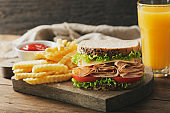 sandwich with ham, french fries and glass of orange juice