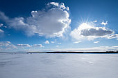 Beautiful winter landscape on the lake. The sun went behind the clouds. The rays of the sun Shine from behind the clouds.