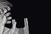 Plastic bag with handles, gloves, on a black background . Used plastic bag for recycling. Concept - ecology, planet pollution with plastic cellophane polyethylene